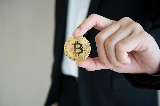 Onherkenbare zakenman die een gouden fysieke bitcoin of btc vasthoudt en toont aan camera met copyspace. bitcoin is de populaire digitale cryptocurrency aangedreven door blockchain-technologie.