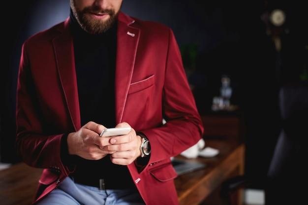Onherkenbare zakenman die smartphone op kantoor gebruikt