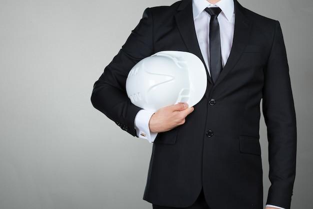 Onherkenbare zakenman die witte bouwvakker houdt