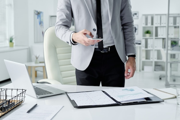 Onherkenbare zakenman die zich aan bureau met laptop bevindt en foto's van documenten neemt terwijl hij zich voorbereidt op een vergadering