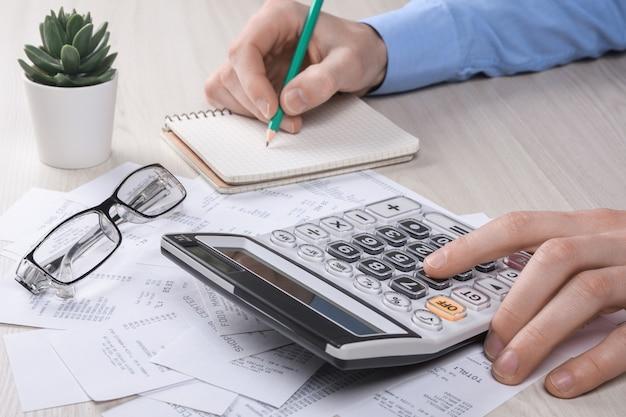 Onherkenbare zakenman met behulp van rekenmachine op bureau kantoor en het schrijven van notitie met berekenen over kosten thuis kantoor