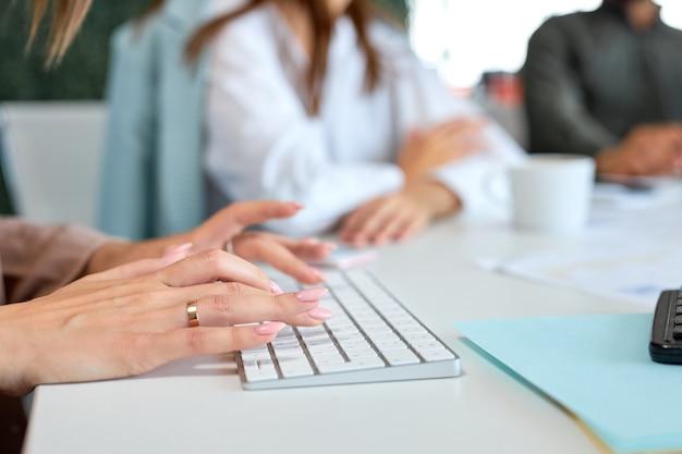 Onherkenbare zakenvrouw op computertoetsenbord, typen, werken op kantoor.