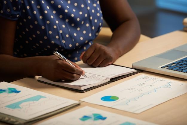 Onherkenbare zwarte dame zittend aan een bureau in het kantoor 's nachts en schrijven in het dagboek