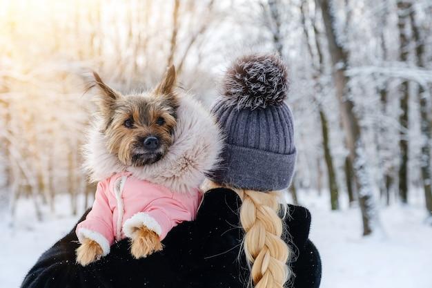 Onherkende vrouw houdt haar geklede hond in haar armen in de winter buiten op wandeling. huisdier zorg concept.