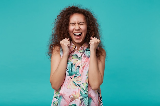 Onjoyed jonge krullende brunette vrouw emotioneel verhogen van haar handen terwijl vreugde over iets met gesloten ogen, geïsoleerd op blauw