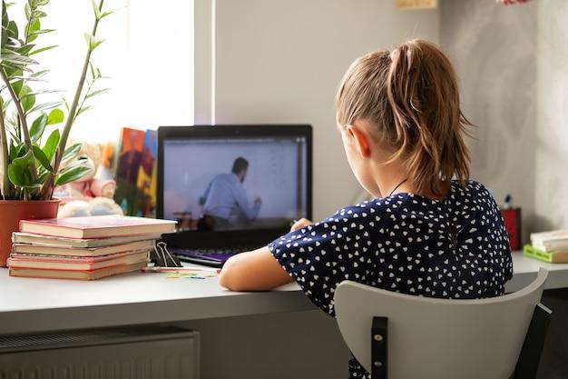 Online afstandsonderwijs, een schoolmeisje met een computer, communiceert met een leraar via videoconferentie.