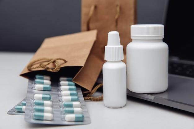 Online apotheekconcept. pillen en spray witte mockup containers en buff papieren zakken over de laptop close-up.