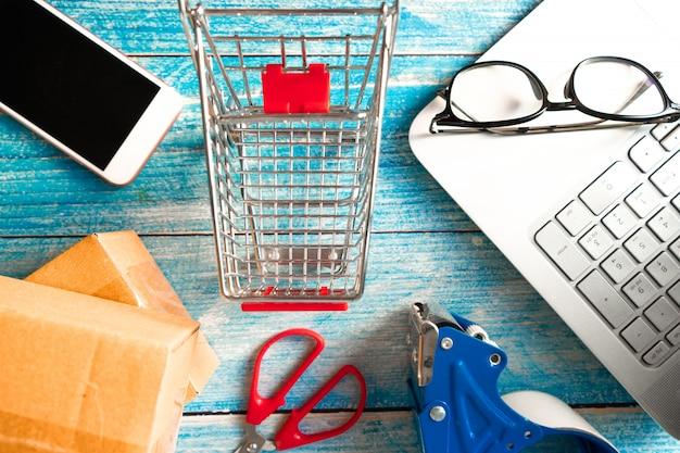 Online bedrijfsconcept. winkelwagen met vakken en smartphone op tafel