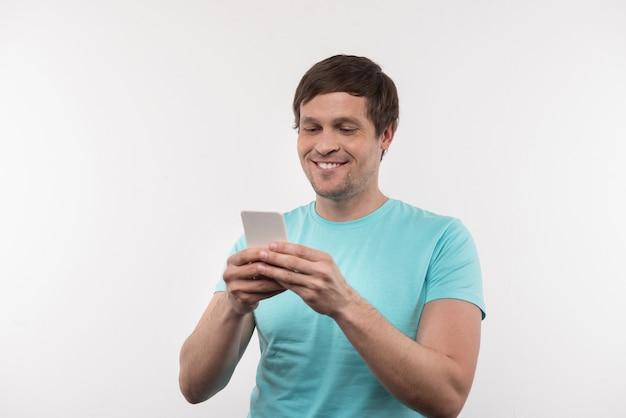 Online berichten. positieve opgetogen man met behulp van zijn mobiele telefoon tijdens het typen van een bericht