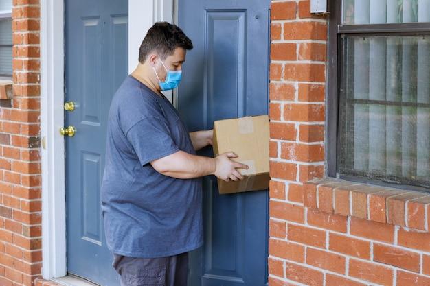 Online bestelling aan huis, man medisch masker met hardwerkende bezorger die een doospakket van de coronavirus-pandemie vasthoudt