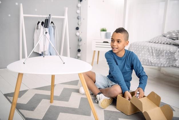 Online bestelling. gelukkig afro-amerikaanse jongen blogger video opnemen tijdens het uitpakken van bestelling