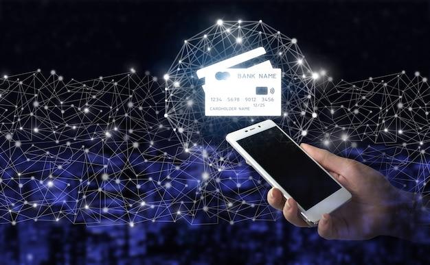 Online betalen digitaal en winkelen op netwerkverbinding. hand houden witte smartphone met digitaal hologram creditcard teken op donkere onscherpe achtergrond van de stad. mobiel bankieren netwerk, online betalen