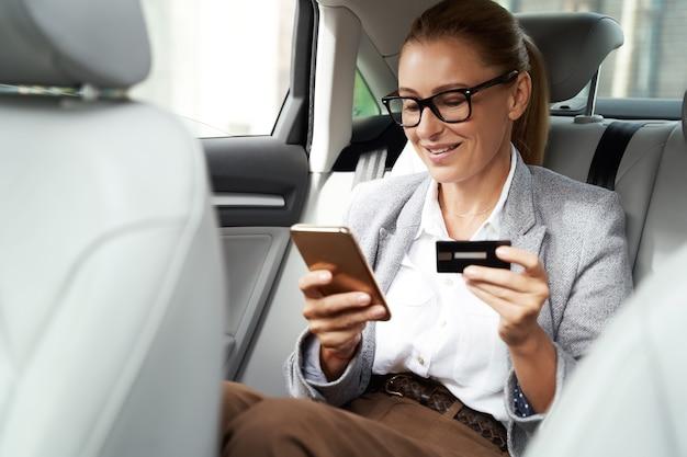 Online betaling glimlachende zakenvrouw die een bril draagt met haar smartphone en creditcard om