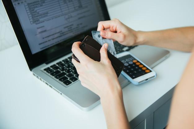 Online betaling, handen van een vrouw met een creditcard en met behulp van een smartphone voor online winkelen