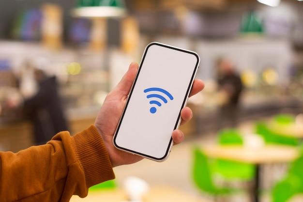 Online betalingen. telefoondisplay met wifi-pictogram tegen de achtergrond van een restaurant