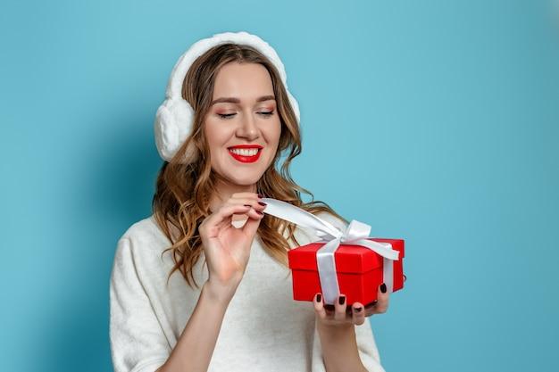 Online cadeaubestelling 2021. close-up portret van jonge glimlachende blanke vrouw die rode geschenkdoos geïsoleerd op blauwe muur te openen en te openen