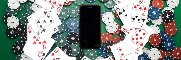 Online casino, mobiel casino, mobiele telefoon, fichekaarten op een groene achtergrond. gokspellen. uitzicht van boven.