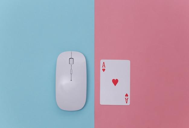 Online casino. pc-muis en aas van harten op roze blauwe achtergrond. bovenaanzicht