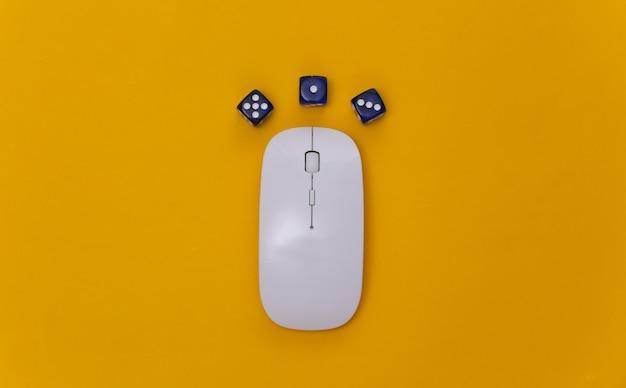 Online casino. pc-muis en dobbelstenen op een gele achtergrond. bovenaanzicht