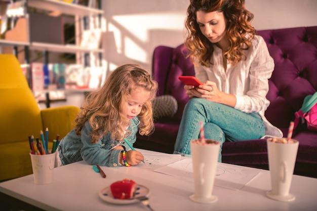 Online chat. raadselachtig kind dat op tafel leunt tijdens het tekenen van een afbeelding