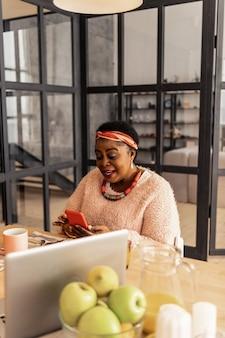 Online chatten. positieve aardige vrouw die een bericht naar haar vriend sms't tijdens het online chatten