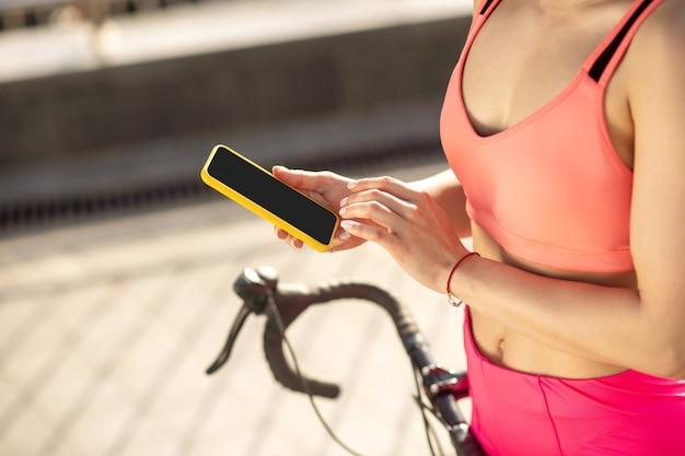 Online. close up van een meisje in sportkleding met een smartphone in handen