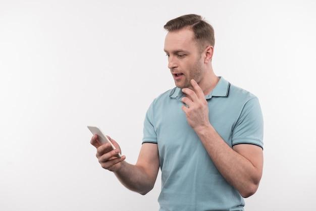 Online communicatie. aardige, aangename man die zijn telefoon vasthoudt terwijl hij berichten controleert