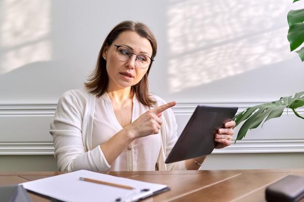 Online communicatie, overleg, opleiding, business. vrouw leraar, mentor, psycholoog kijken naar webcam van tablet, praten, counseling, aantekeningen maken op papier. technologie afstand levensstijl