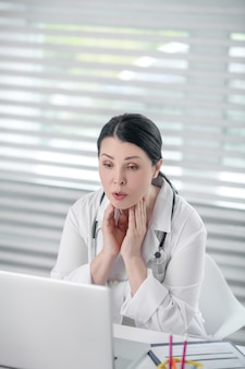 Online consult. slimme donkerharige vrouw in een medische jas kijken naar het scherm van de laptop, serieus praten.