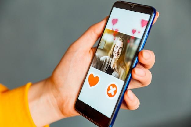 Online dating-app op smartphone. man kijkt naar foto van mooie vrouw.
