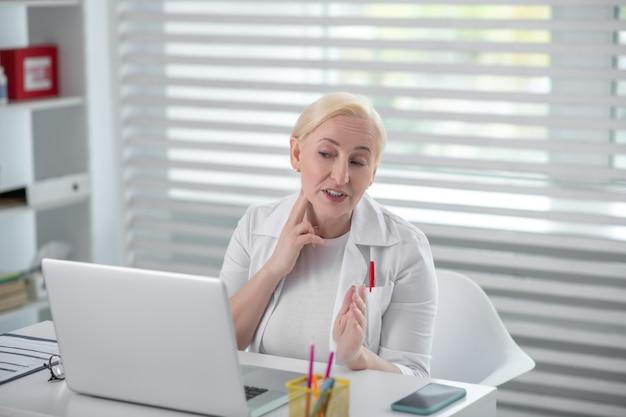 Online doktersconsult. blondevrouw in een medische laag die voor laptop zitten, houdend een hand dichtbij haar hals, het vertellen counseling.
