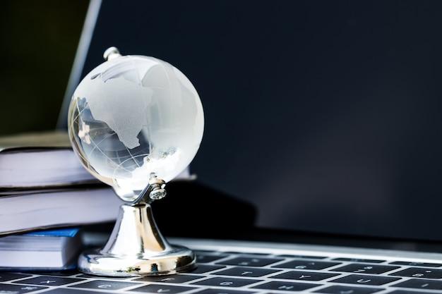 Online e-learning onderwijs door technologieconcept amerika glazen aardebol op computer laptop toetsenbord