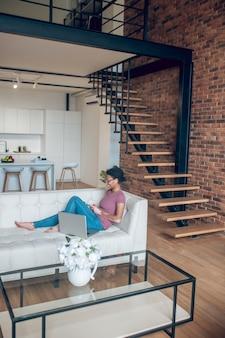 Online. een vrouw in vrijetijdskleding die op internet surft terwijl ze thuis rust