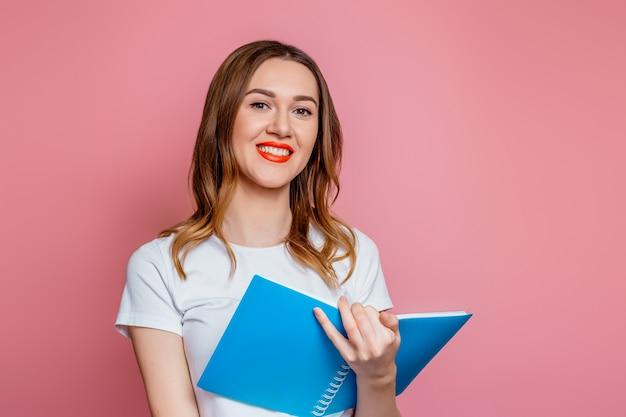 Online engelse lessen. jonge vrouw leraar houden blocnote voor notities glimlachend geïsoleerd op roze achtergrond