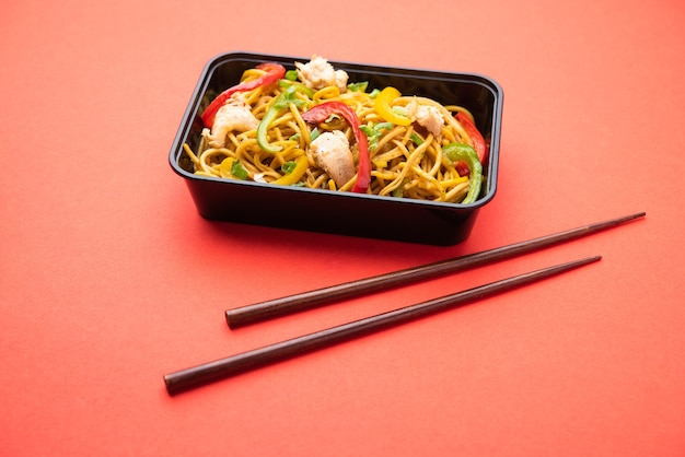 Online eten bestellen, bezorgen in india - schezwan noodles, kip hakka noodles verpakt in plastic doos