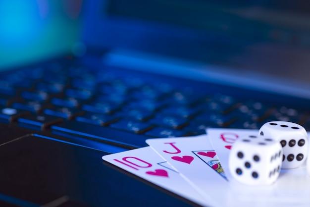 Online gamingplatform, casino en gokbedrijf. kaarten en dobbelstenen op laptop toetsenbord, afgezwakt in blauw.