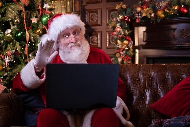 Online gefeliciteerd met de kerst van de kerstman. kerstman met laptop laptop voor afstand