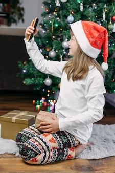Online gefeliciteerd met nieuwjaar en kerstmis. leuk glimlachend meisje gebruikt mobiele telefoon voor online videochat, bel naar ouders, familie of vrienden.