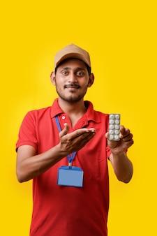 Online geneeskundeconcept: indiase bezorger die medicijnstrip in de hand houdt