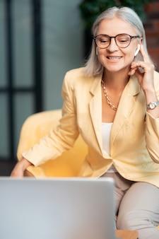 Online gesprek. succesvolle zakenvrouw met een draadloze headset die deelneemt aan een online gesprek zittend in een gele leunstoel voor een laptop