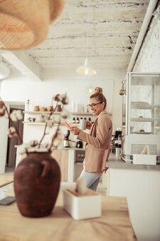 Online grappen maken. glimlachende vrouw beantwoordt haar grappige berichten terwijl ze naar de tablet kijkt en koffie drinkt.