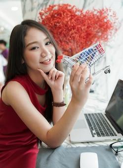 Online het winkelen concept - mooie vrouw het glimlachen holdingskar en creditcard terwijl het winkelen op laptop