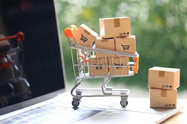 Online inkomen, bruine pakketdoos en model miniatuur winkelwagentje op computertoetsenbord voor online winkelen