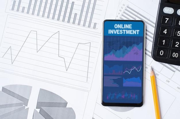 Online investering. smartphone met een mobiele app op de achtergrond van grafieken en diagrammen