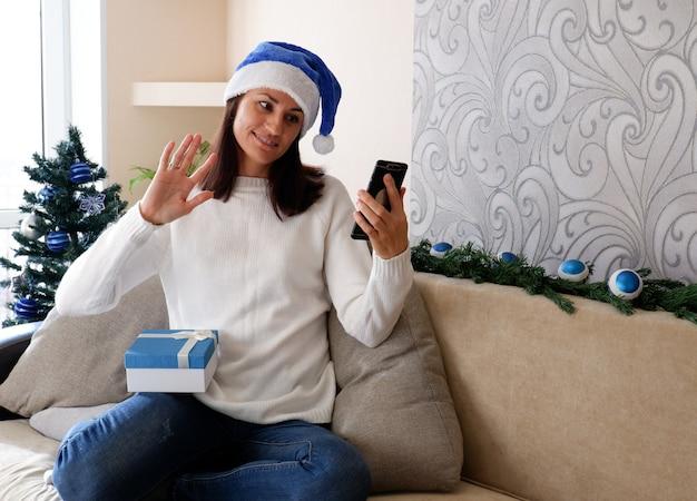 Online kerstgroeten. een vrouw met een telefoon thuis in een kerstmuts feliciteert vrienden.