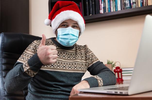Online kerstgroeten. jonge man in kerstman hoed praat met laptop voor videogesprek vrienden en kinderen. de kamer is feestelijk versierd. kerst tijdens coronavirus.