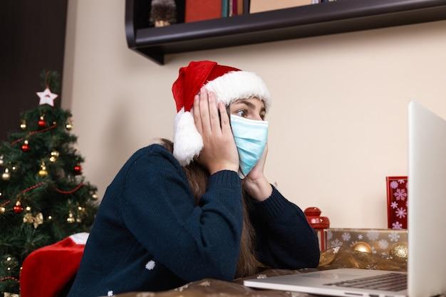 Online kerstgroeten. meisje in kerstman hoed in medische masker gesprekken geeft een cadeau met laptop voor video-oproep vrienden en ouders. de kamer is feestelijk versierd. kerst tijdens coronavirus.