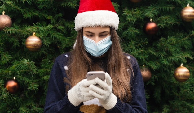 Online kerstgroeten. sluit omhoog portret van vrouw die een hoed van de kerstman en medisch masker met emotie draagt. tegen de achtergrond van een kerstboom. coronapandemie