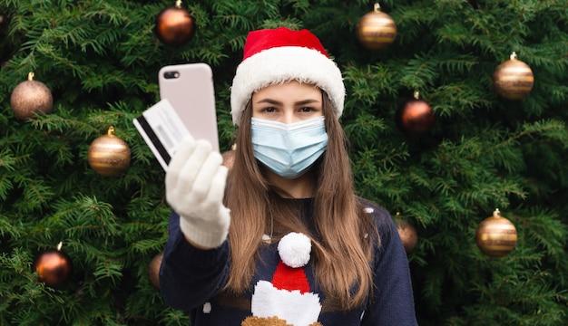 Online kerstinkopen. sluit omhoog portret van vrouw die een hoed van de kerstman en medisch masker met emotie draagt. tegen de achtergrond van een kerstboom. coronapandemie