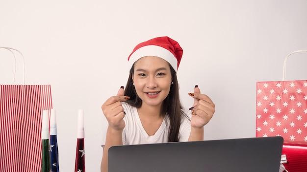 Online kerstviering met tiener aziatische vrouw feest x mas en nieuwjaar in lockdown coronavirus quarantaine covid nieuw normaal sociaal afstand communicatie op afstand verblijf thuis roeping
